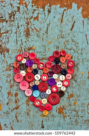 Red heart background on vintage old surface.Old colorful buttons/Valentines day background