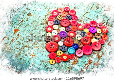 Red heart background on vintage old surfaces.Old colorful buttons/Valentines day background