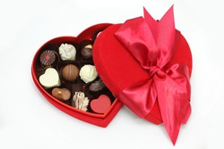red heart box of assorted heart pralines in white background