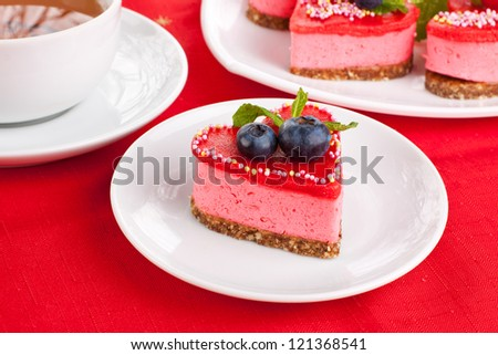 Red heart cake with cup of tea and plate of cakes on background