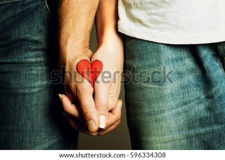 red heart drawing on hands of a couple holding hand in hand, lovers, symbol of love, togetherness, hands holding, love, valentine #596334308