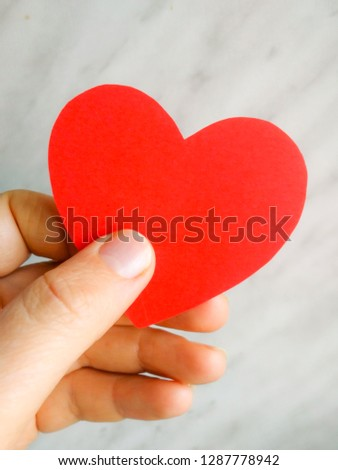 Red heart from paper in hand as a symbol of love, care, gift #1287778942