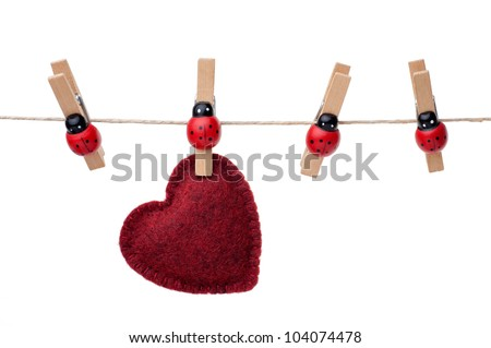 Red heart hanging on a clothesline, four pins, white background