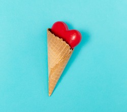 Red heart in a cornet, on blue background. Conceptual solution.