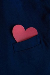 Red heart in a jacket pocket for Valentine's Day. Father's Day. A heart that symbolizes love.