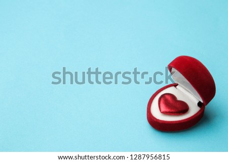 Red heart in a red gift box on a bright blue background close-up. space for text #1287956815