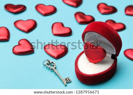 Red heart in a red gift box with a key and small hearts on a bright blue background close-up #1287956671