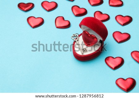 Red heart in a red gift box with a key and small hearts on a bright blue background close-up. space for text #1287956812