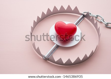 Red heart in a trap on pink background. Online internet romance scam or valentine day in darkside concept. Love is bait or victim. #1465386935