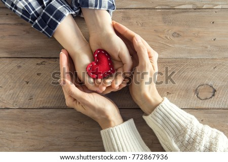 Red heart in child and female hands over wooden background, copy space. Kindness, family, love and charity concept, hand made valentine or mother's day gift.
