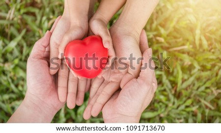 Red heart in family hands on green grass background, adult and child hands holding red heart, health care, donate family insurance concept, Earth day together harmony peaceful concept. #1091713670
