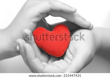 Red heart in gentle hands. #215447431