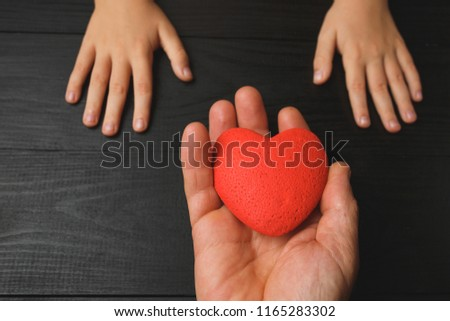 red heart in hands on a dark background, the concept of love and care for loved ones and needy #1165283302