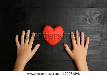 red heart in hands on a dark background, the concept of love and care for loved ones and needy #1170971698