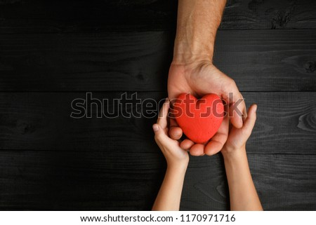 red heart in hands on a dark background, the concept of love and care for loved ones and needy #1170971716