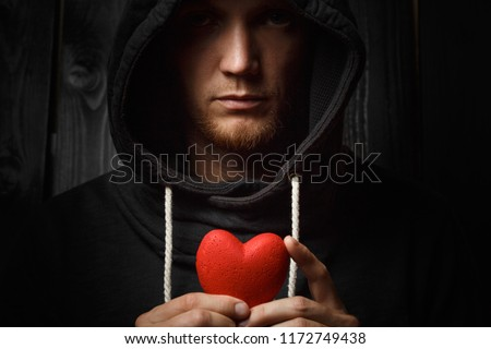 red heart in hands on a dark background, the concept of love and care for loved ones and needy #1172749438