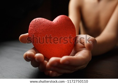 red heart in hands on a dark background, the concept of love and care for loved ones and needy #1172750110