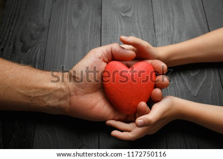red heart in hands on a dark background, the concept of love and care for loved ones and needy #1172750116
