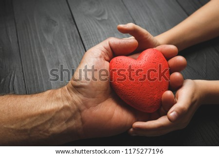 red heart in hands on a dark background, the concept of love and care for loved ones and needy #1175277196