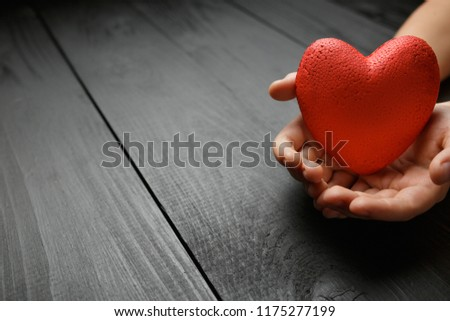 red heart in hands on a dark background, the concept of love and care for loved ones and needy #1175277199