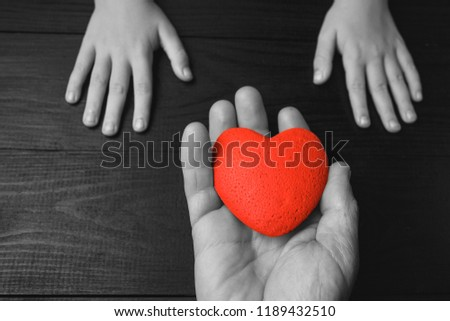 red heart in hands on a dark background, the concept of love and care for loved ones and needy.black and white. #1189432510