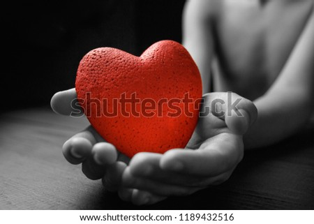 red heart in hands on a dark background, the concept of love and care for loved ones and needy.black and white. #1189432516