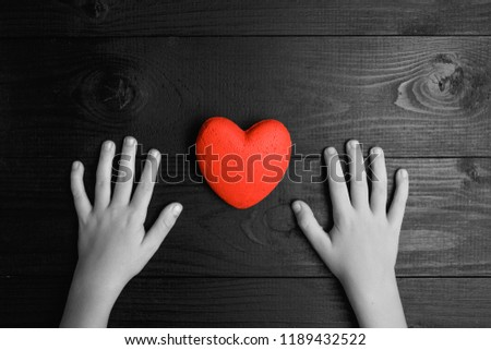 red heart in hands on a dark background, the concept of love and care for loved ones and needy.black and white. #1189432522