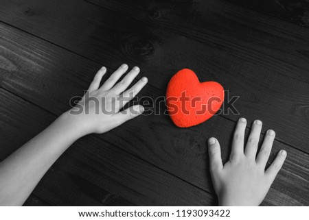 red heart in hands on a dark background, the concept of love and care for loved ones and needy.black and white. #1193093422
