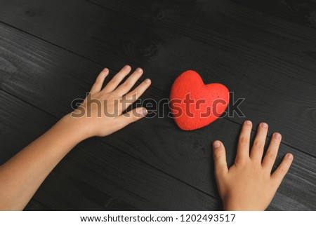 red heart in hands on a dark background, the concept of love and care for loved ones and needy #1202493517