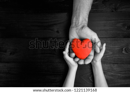 red heart in hands on a dark background, the concept of love and care for loved ones and needy.black and white. #1221139168