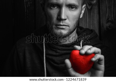 red heart in hands on a dark background, the concept of love and care for loved ones and needy.black and white. #1224671839