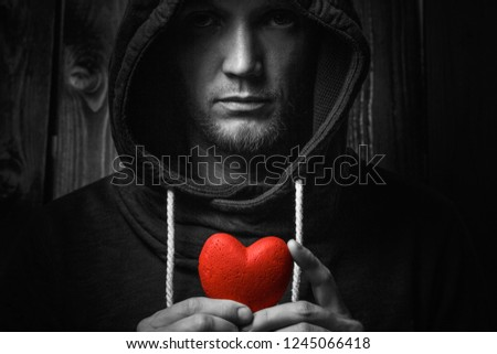 red heart in hands on a dark background, the concept of love and care for loved ones and needy.black and white. #1245066418