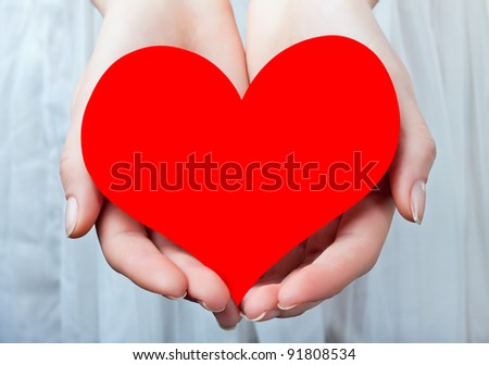 Red heart in her hands, on a light background