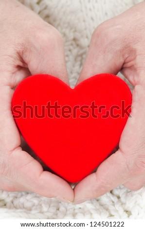 red heart in the hands of men closeup vertical