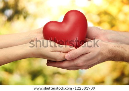 Stock Photo Red heart in woman and man hands, on green background