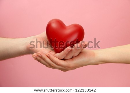 Red heart in woman and man hands, on pink background