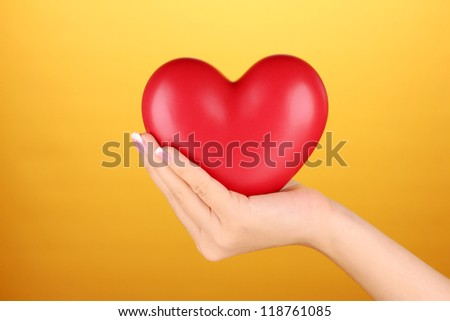 Red heart in woman's hand, on orange background close-up