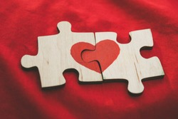 Red heart is drawn on the pieces of the wooden puzzle lying next to each other on red background. Love concept. St. Valentine day