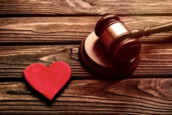 red heart, judge hammer on wooden table background.  family law.