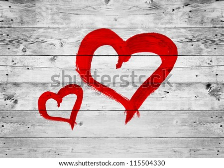 Red heart love symbol painted on old wooden grey wall background - stock photo