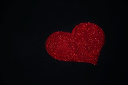 Red heart made of sequins on a black background. Glyph of Shimmering Dust