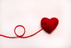 Red heart made of wool on a white background