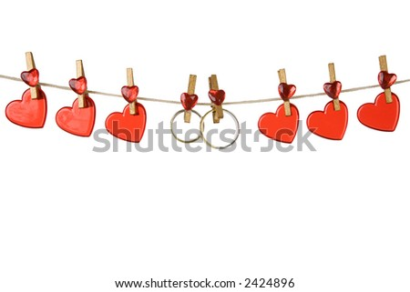 red heart on a clothesline with gold-colored clothes pin on white background