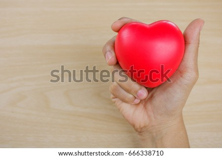 Red heart on hand on wooden background. #666338710