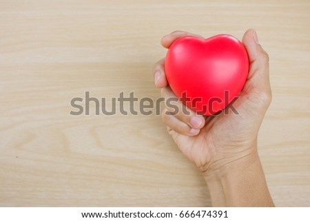 Red heart on hand on wooden background. #666474391