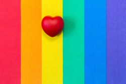 Red heart on rainbow flag pattern of fabric texture for LGBTQ. Rainbow flag pattern of fabric for LGBT pride and red heart shape. Homosexual texture flag. Love and freedom concept. Copy space