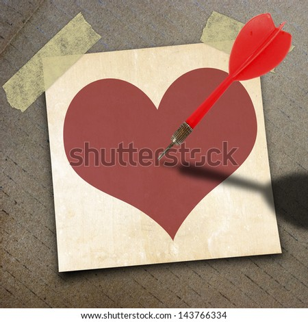 red heart on short note paper and red dart on the packing paper box texture background