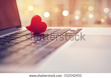 Red heart on the computer keyboard with sunlight and shadow. Internet dating, copyspace, Valentines day concept.