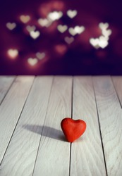 Red heart on white boards against a bokeh background