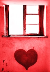 red heart painted on white dirty wal. opened window.